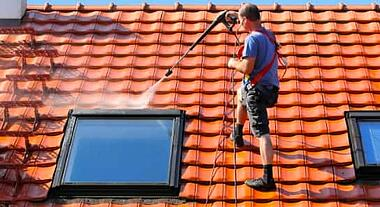 Person pressure washing a roof with sky light windows